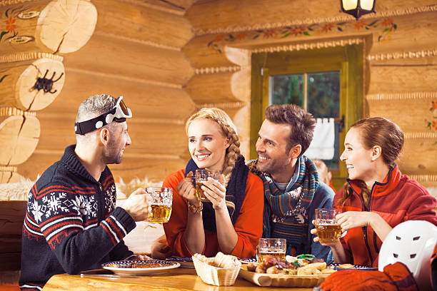 Friends having dinner in restaurant after skiing Two adult couples wearing winter clothes sitting in a mountain restaurant after skiing, having chat, enjoying dinner and drinking beer.  apres ski stock pictures, royalty-free photos & images