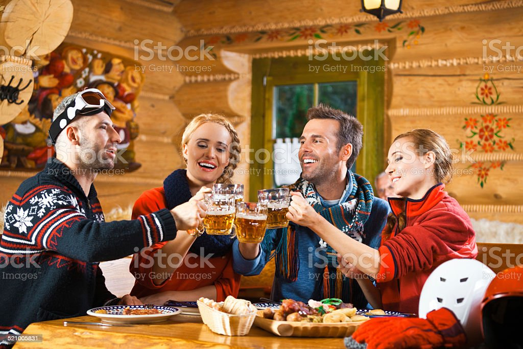 Friends having dinner in restaurant, toasting with beer Two adult couples wearing winter clothes sitting in a mountain restaurant after skiing, enjoying dinner and toasting with beer. Adult Stock Photo
