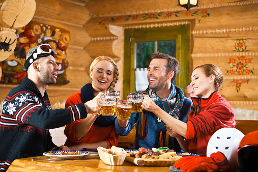 Friends Having Dinner In Restaurant Toasting With Beer Stock Photo - Download Image Now