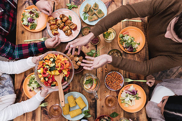 friends having dinner. - dining table stock photos and pictures