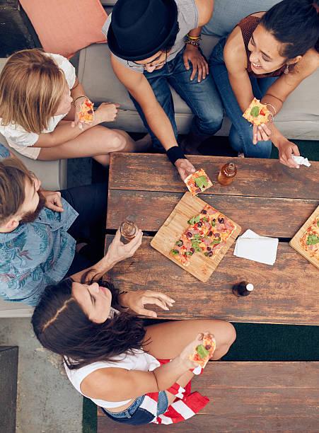 Amigos tendo bebidas e pizzas no party - foto de acervo