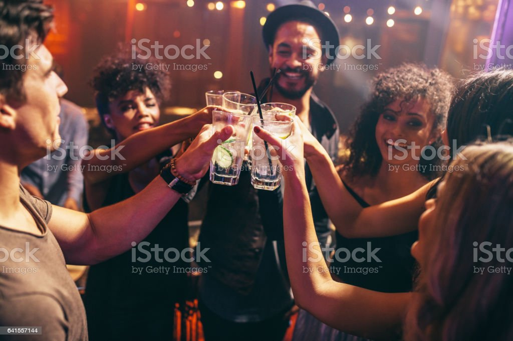 Friends having drinks at the night club party stock photo