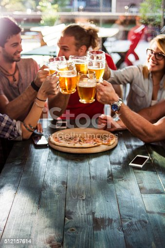 Group of friends having drinks in a pub. Focus is on foreground.