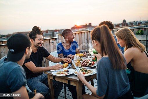 Group of young men and women sitting around table on roof and eating food. Friends having food at rooftop party.