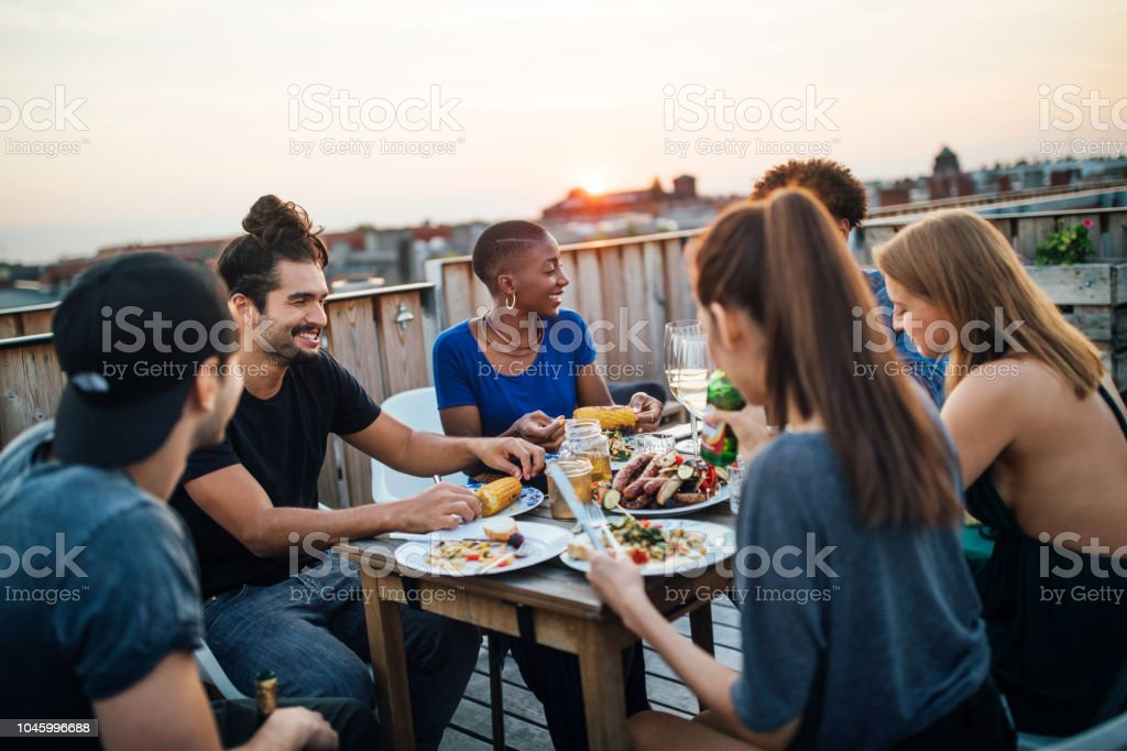 Friends having food at rooftop party stock photo