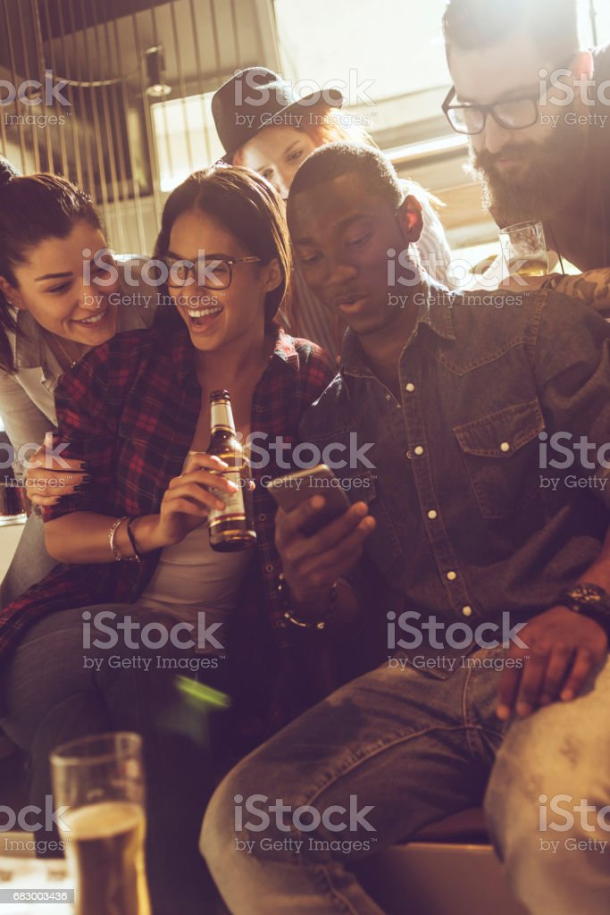 friends having fun and playing with the smartphone royalty-free stock photo