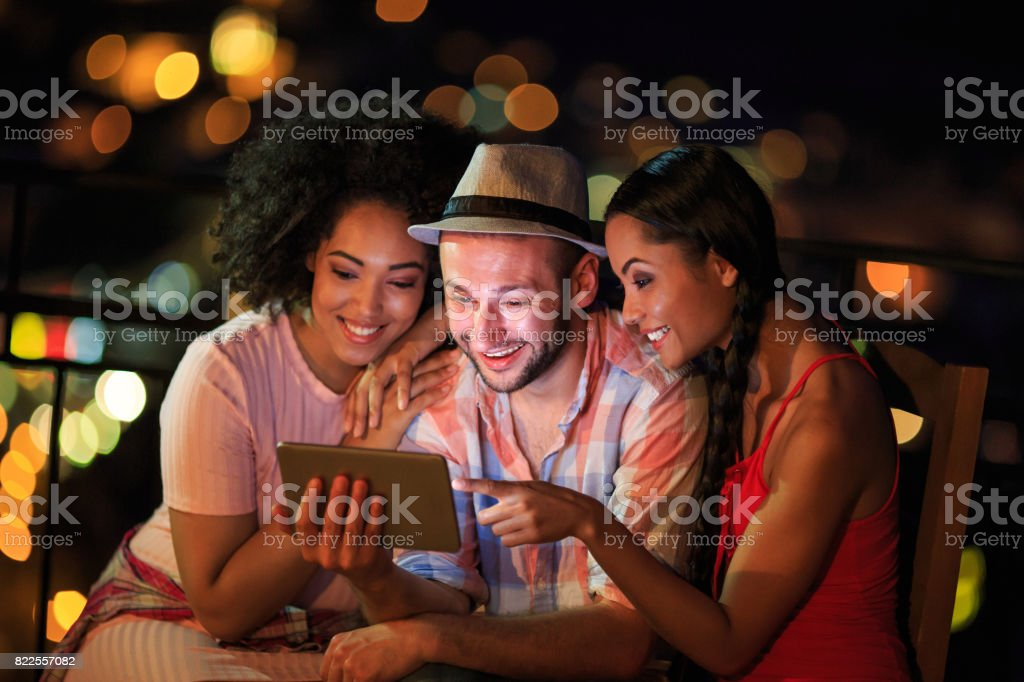 Friends having fun and using tablet at night stock photo