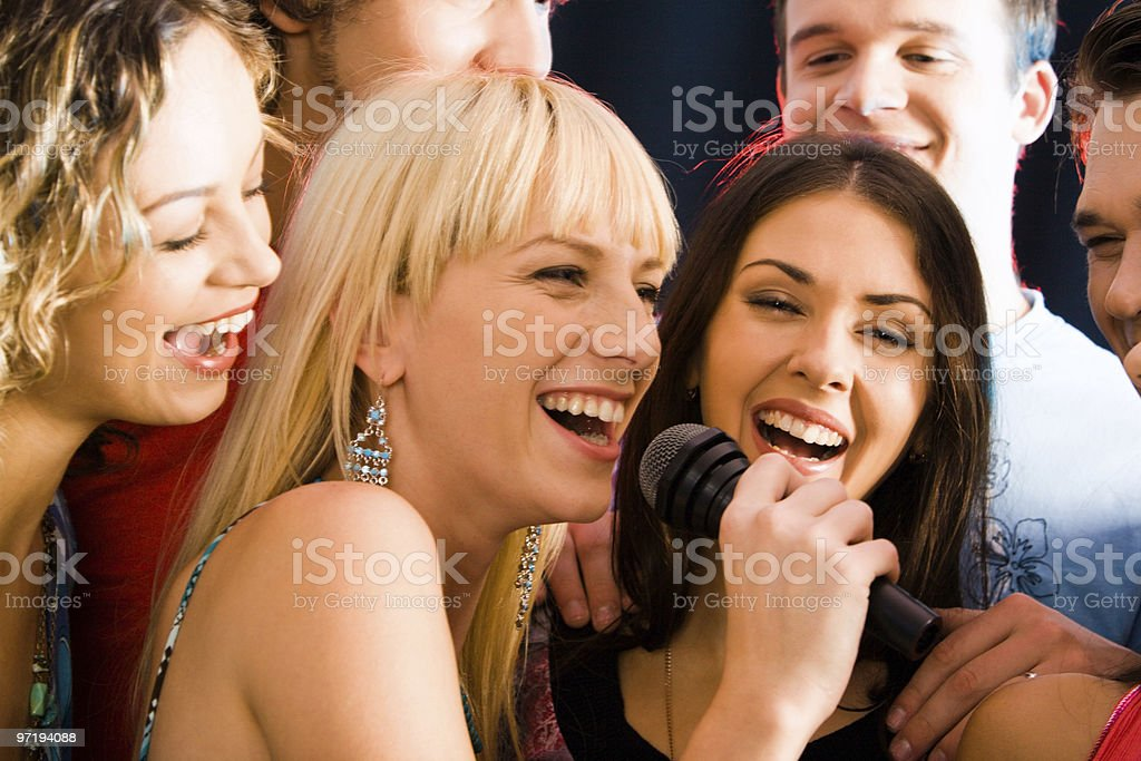 Friends having fun at karaoke party stock photo