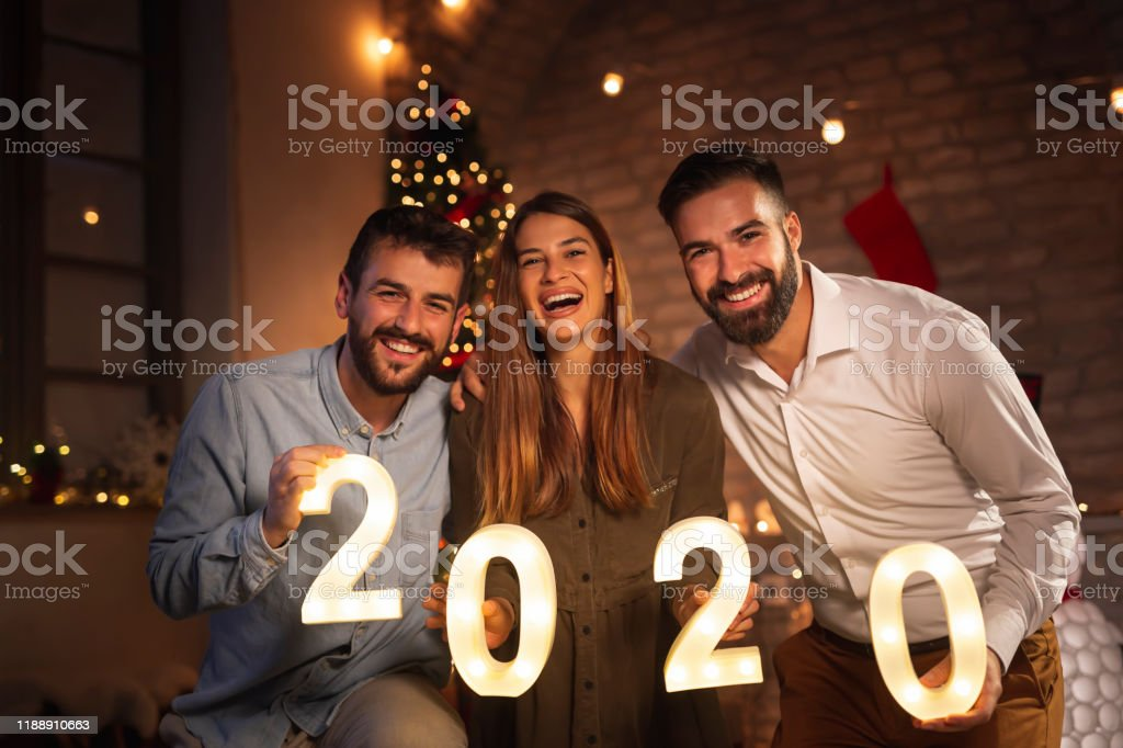 Group of young friends having fun at New Years party, holding...