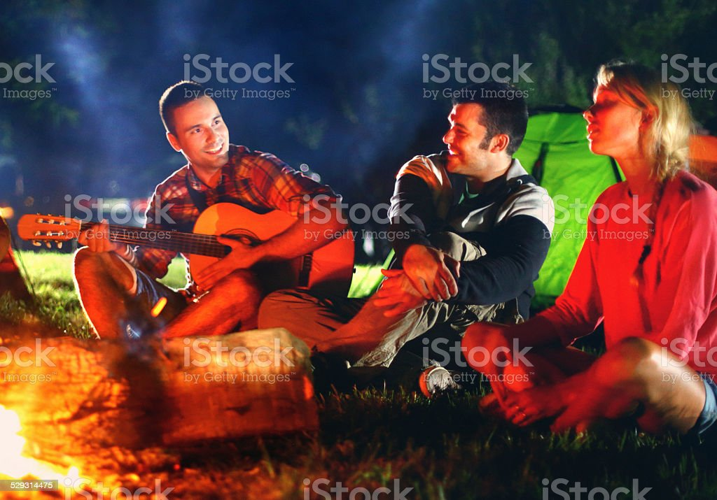 Group of friends singing and having fun by campfire.