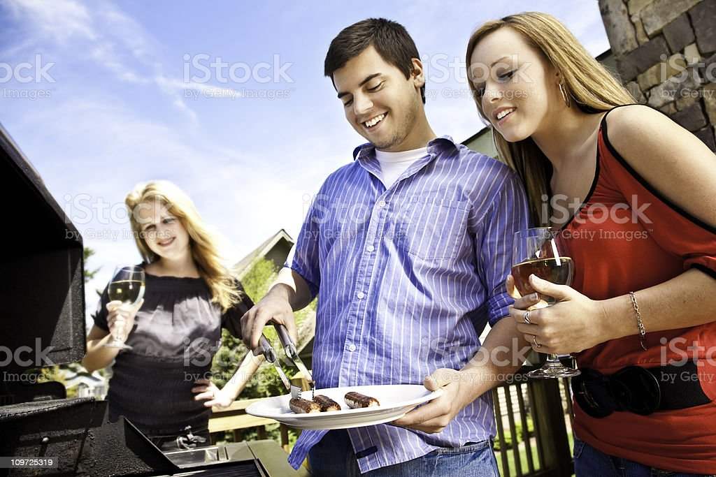 Friends Having Fun Cooking Hot Dogs on House Patio Grill royalty-free stock photo