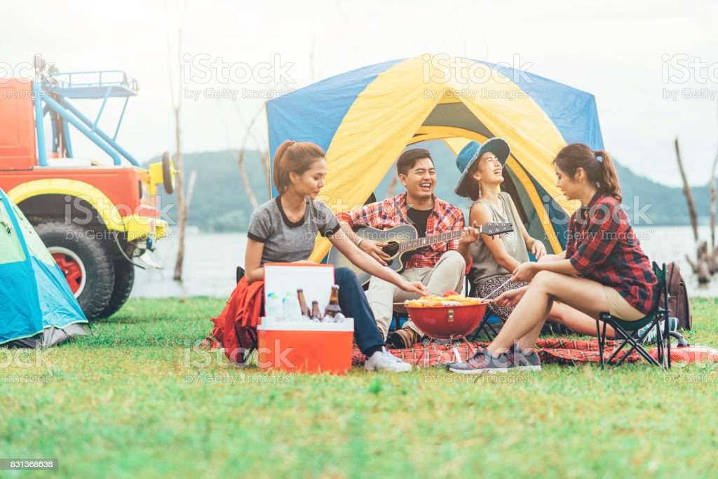 friends having fun eating barbecue outdoor while camping stock photo