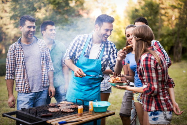 friends having fun grilling meat enjoying bbq party - barbecue grill stock photos and pictures