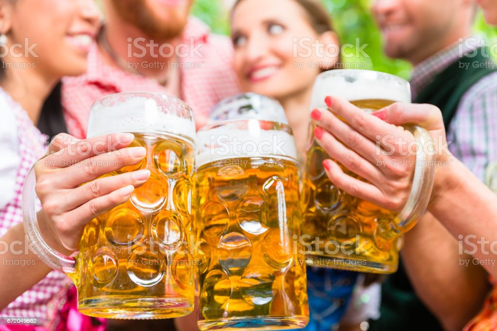 Friends having fun in beer garden while clinking glasses stock photo