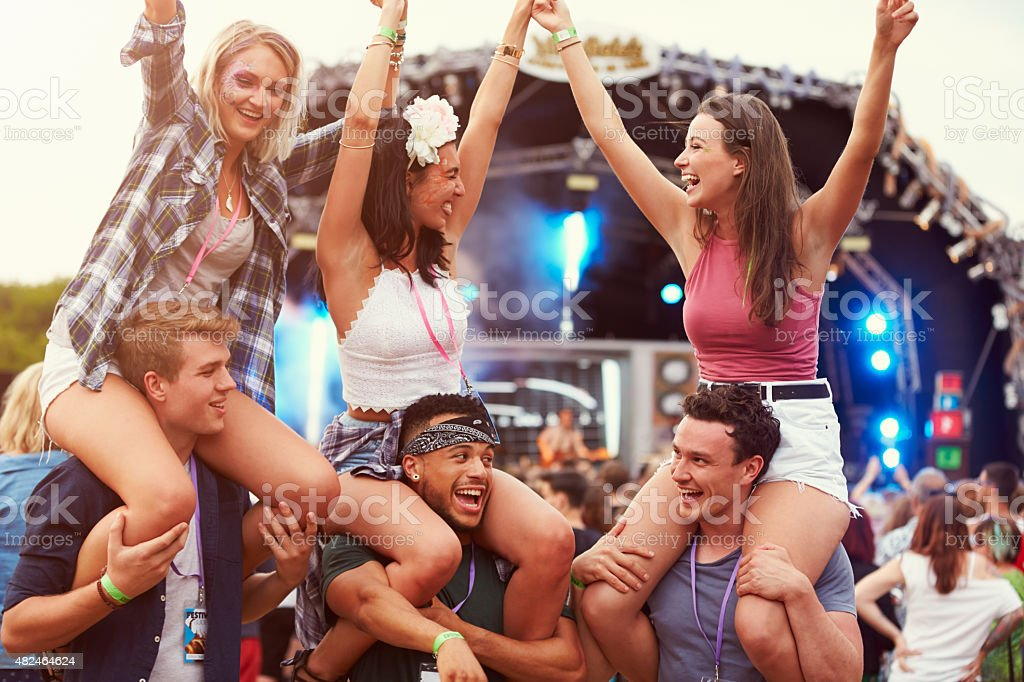 Friends having fun in the crowd at a music festival stock photo