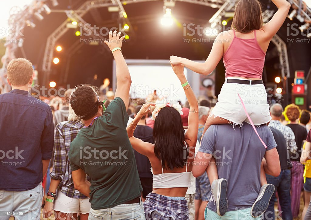 Friends having fun in the crowd at music festival stock photo