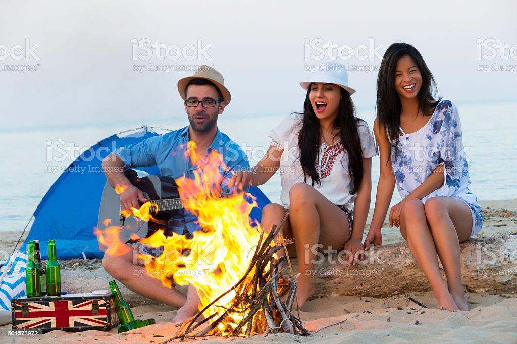 Friends having fun near the bonfire while camping on beach stock photo