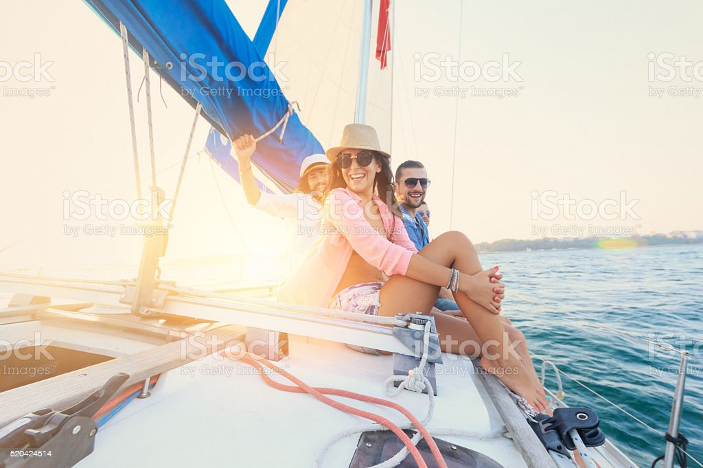 Friends having fun on sailboat. stock photo