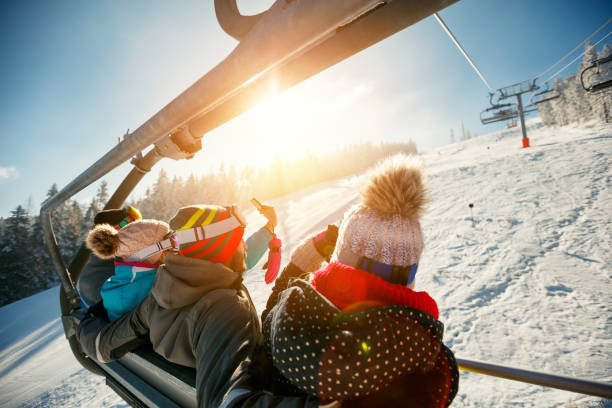 friends having fun on ski holiday in mountains stock photo