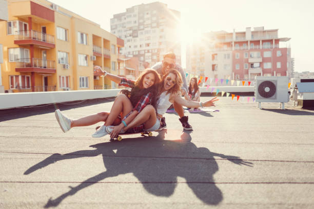 Friends having fun on the rooftop Young people skateboarding on the roof leisure equipment stock pictures, royalty-free photos & images
