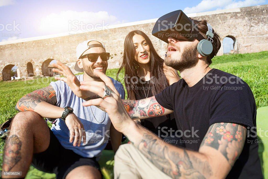 Amigos se divertindo ao ar livre no parque com fones de ouvido contra vibração foto royalty-free