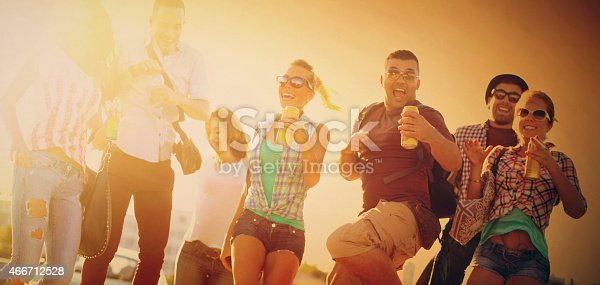 Group of mid 20's people having fun.Jumping and laughing while looking at camera.There are three guys and four girls.Drinking canned drinks. Front view, toned image.