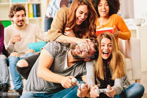 Cheerful Group Of Young Friends Playing Video Games At Home