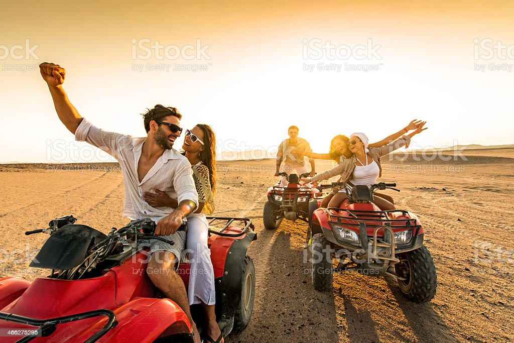 Friends having fun riding quad bikes in desert stock photo