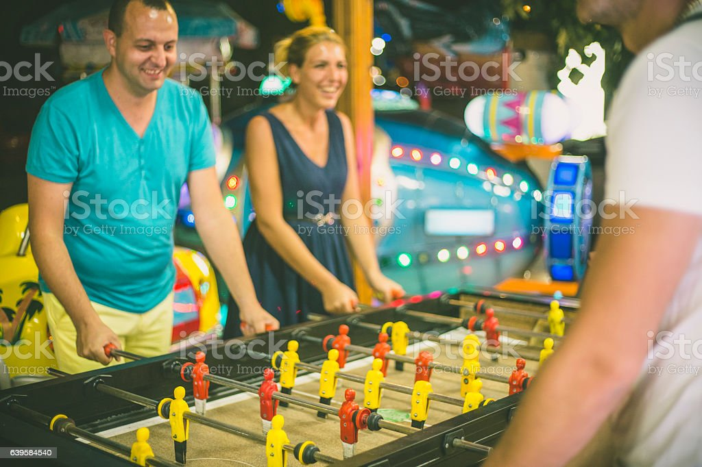 Friends having fun together playing table football. stock photo