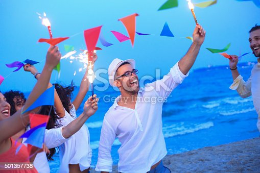 471113366istockphoto Friends having fun with fireworks and decoration on the beach 501357738