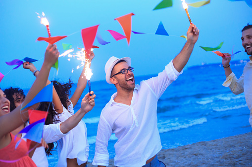 471113366 istock photo Friends having fun with fireworks and decoration on the beach 501357738