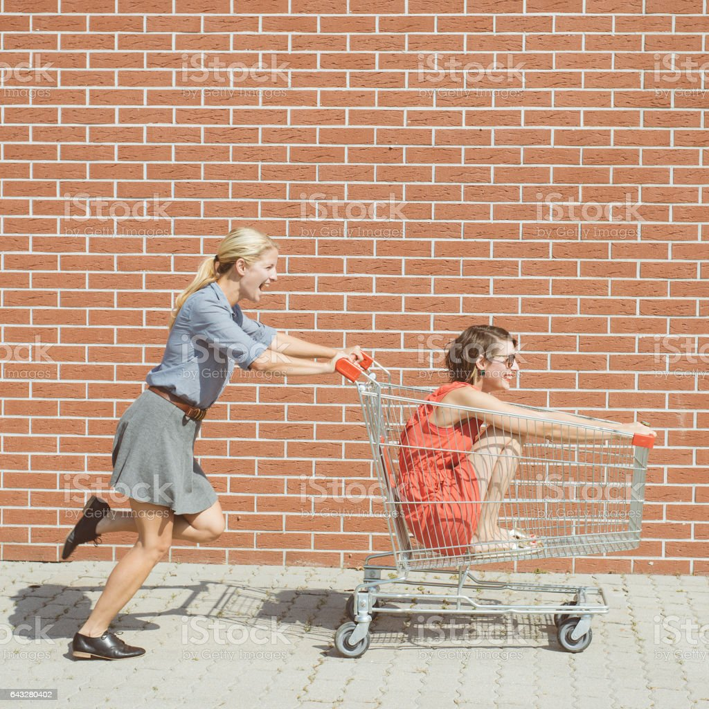 Friends having fun with shopping cart at a mall stock photo