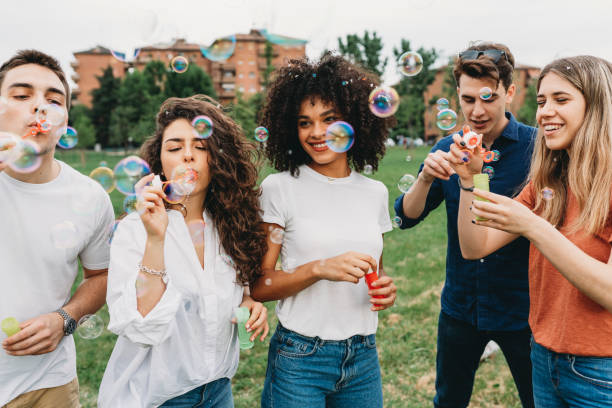 Friends having fun with soap bubbles together at the park stock photo