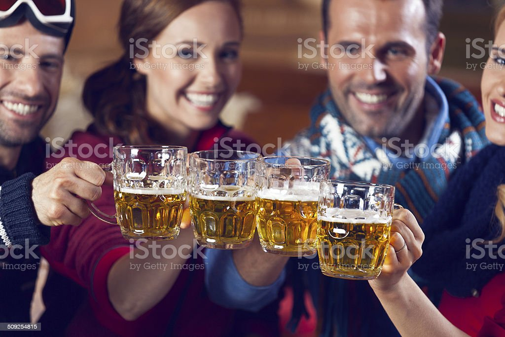 Friends Having Good Times Group of friends wearing warm clothes toasting with beer. Focus on beer glasses. Adult Stock Photo