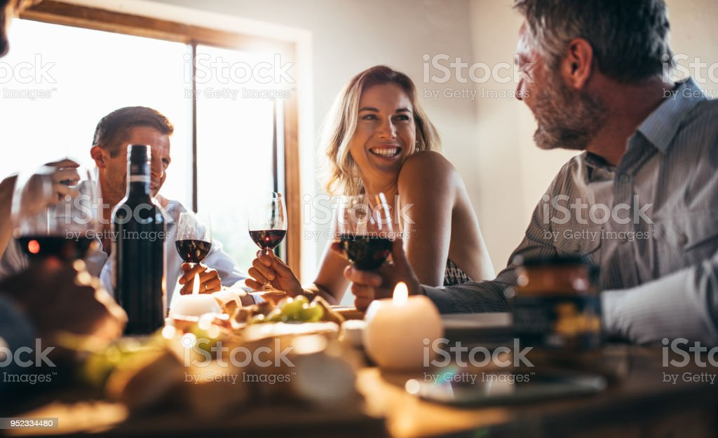 Friends having great time at dinner party stock photo