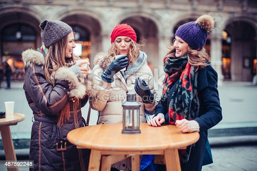 Friends drinking hot wine outdoors at winter city street, christmas market. Wearing warm clothes. Vienna, Austria. Smiling and talking.