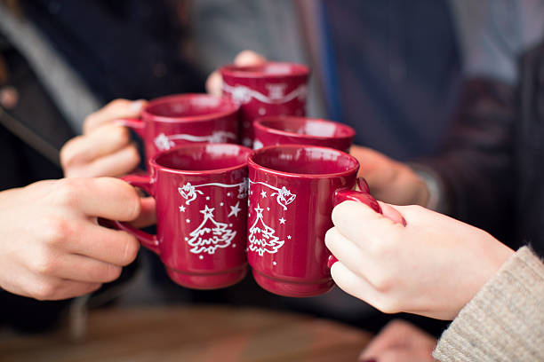 friends having hot drinks outdoors in winter city. - mulled wine stock photos and pictures