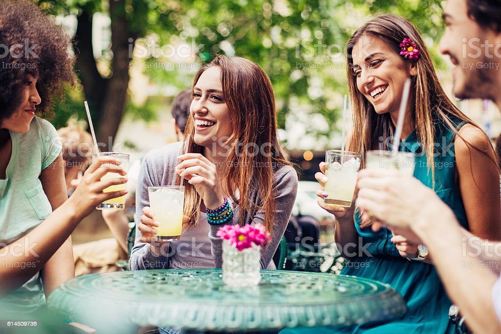 Friends having iced drinks outdoors stock photo