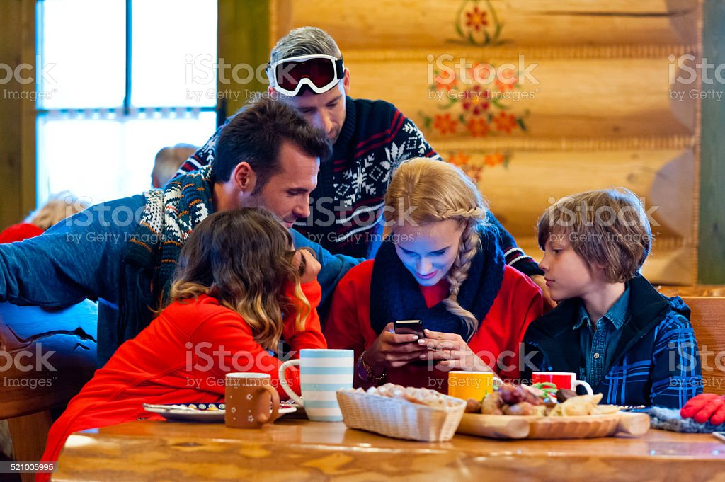 Friends having lunch after skiing, using a smart phone Group of friends wearing winter clothes sitting in a mountain restaurant after skiing, having lunch, woman using a smart phone. Adolescence Stock Photo