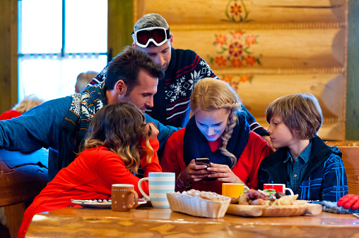 Friends Having Lunch After Skiing Using A Smart Phone Stock Photo - Download Image Now