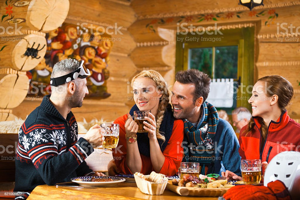 Friends having lunch and drinking beer after skiing Two adult couples wearing winter clothes sitting in a mountain restaurant after skiing, talking, enjoying dinner and drinking beer.  Adult Stock Photo