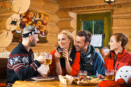 Friends Having Lunch And Drinking Beer After Skiing Stock Photo - Download Image Now