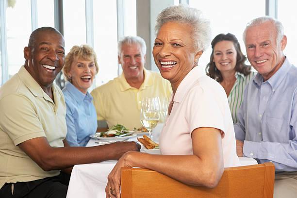 friends having lunch together at a restaurant - sağlıklı yaşlılar stok fotoğraflar ve resimler