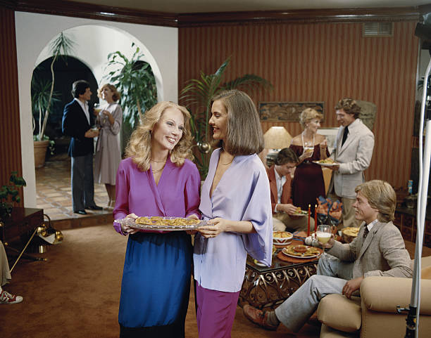 freunde mit party im wohnzimmer, lächelnd - 80er outfit stock-fotos und bilder