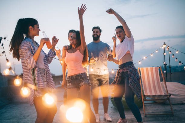 Friends having party on top of the roof. Fun, summer, city lifestyle and friendship concept stock photo