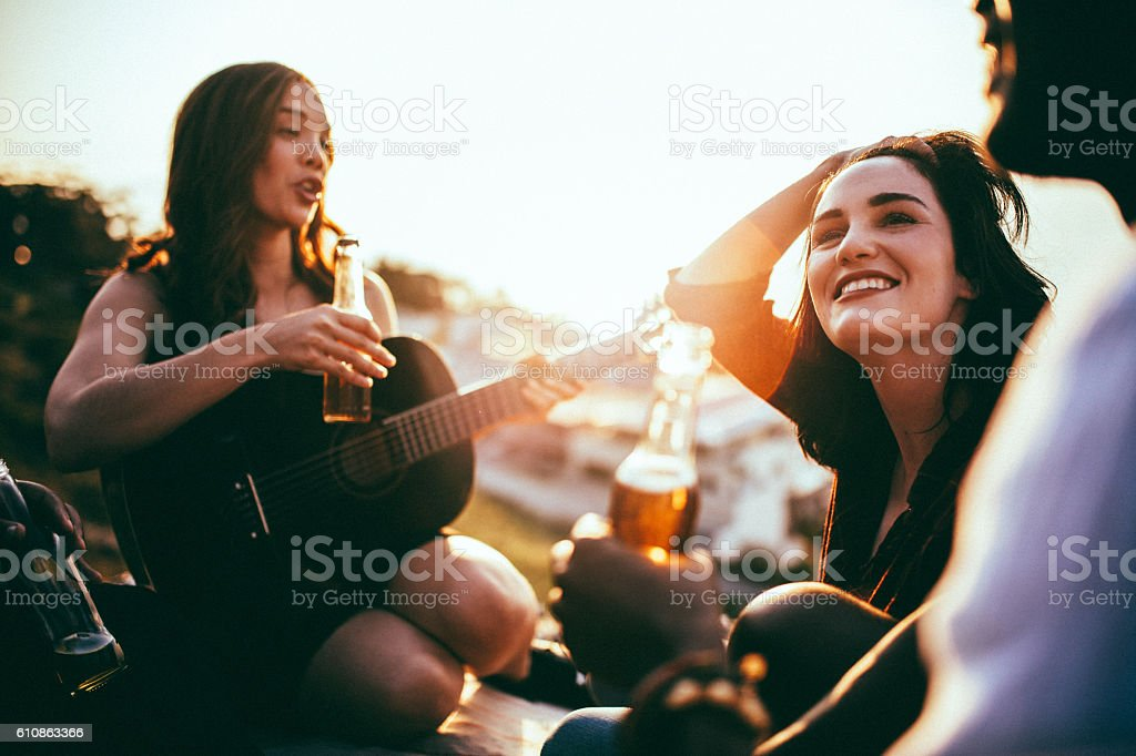 Friends having picnic and listening to music played on guitar stock photo