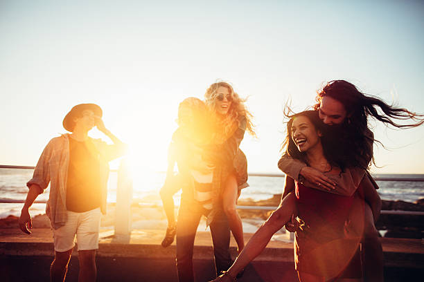 Friends having piggyback rides on beach at sunset stock photo