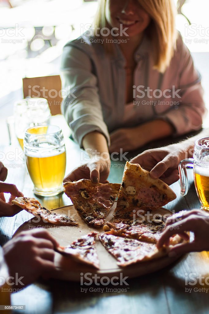 Friends having pizza in a restaurant stock photo