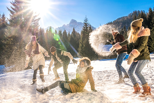 Friends having snowball fight out in snow on sunny day
