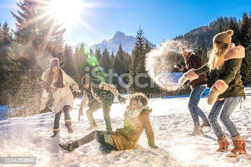Women and men having snowball fight in snow on sunny day.